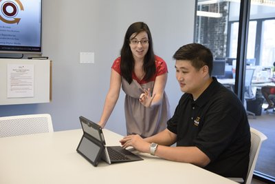 Librarian Emily Treptow (left) shows business resources to entrepreneur Andrew Kim, President of HaulHound.com, at the Polsky Innovation Exchange. (Photo by Joel Wintermantle)