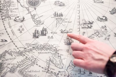 A hand points at an Arctic expedition map