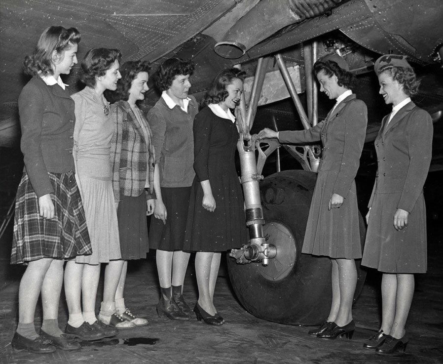 Women standing by an airplane wheel on the runway