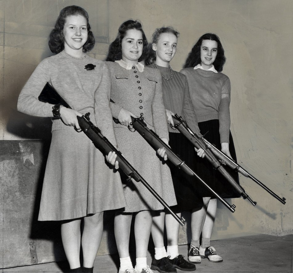 Four women holding rifles at ease.
