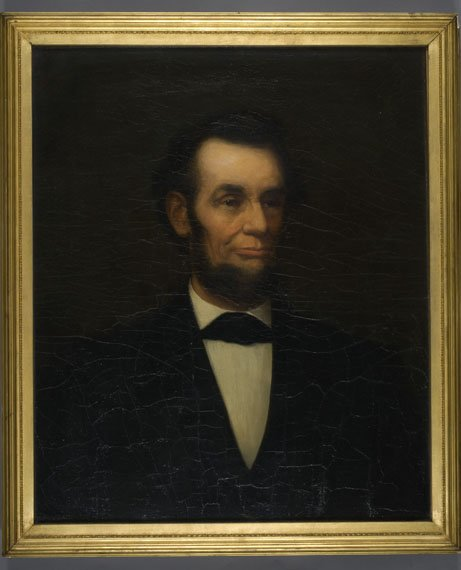 A dark, muted portrait of a skinny, suited man with a trim beard.