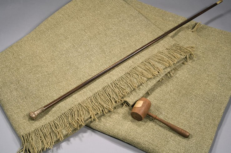 A smooth fringed piece of cloth lies under a polished, thin wooden stick and a lighter-colored gavel.