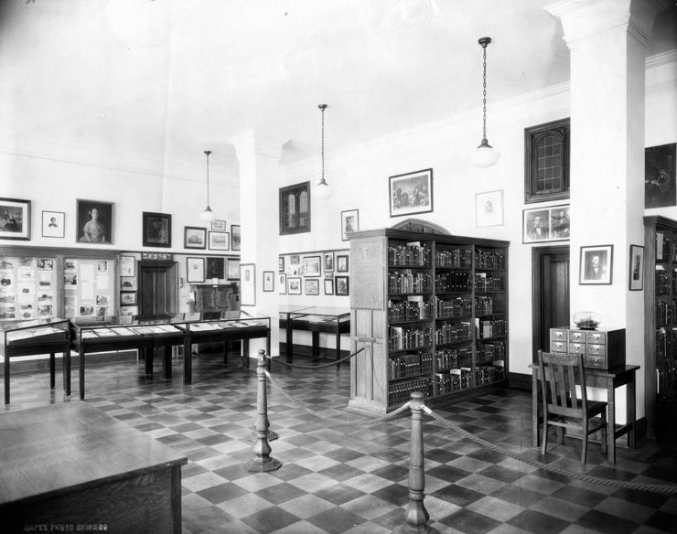 An old photograph of a room with glass cases, a bookcase, and various portraits.