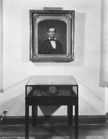 A framed portrait of Abraham Lincoln above a glass case.