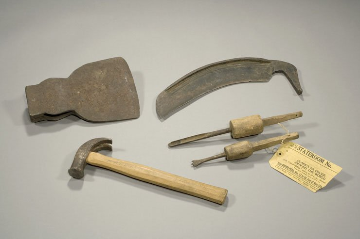 An assortment of sharp though rusted metal tools.