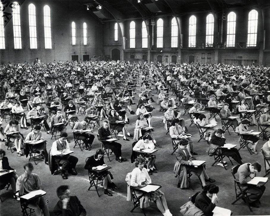 Large room full of students seated at desks taking an exam