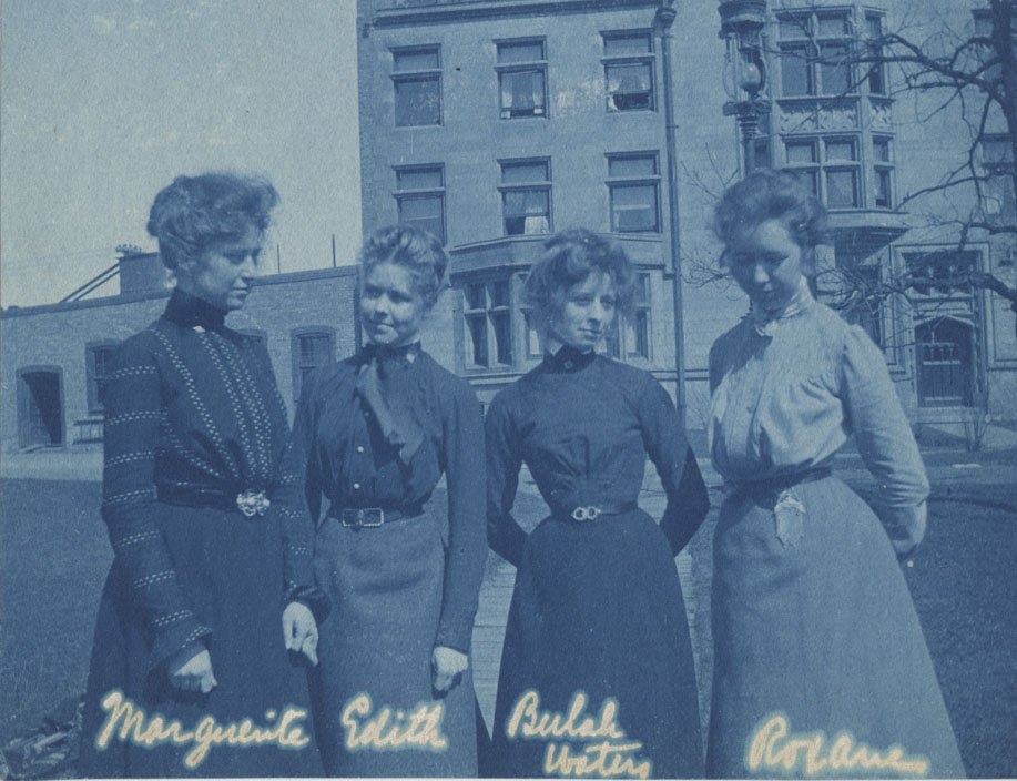 Well dressed women standing in front of a UChicago building