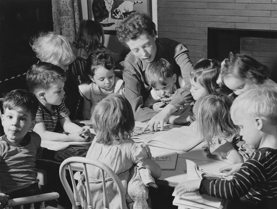 Woman reading a story to a group of children. Child in center of photo is totally picking his nose.
