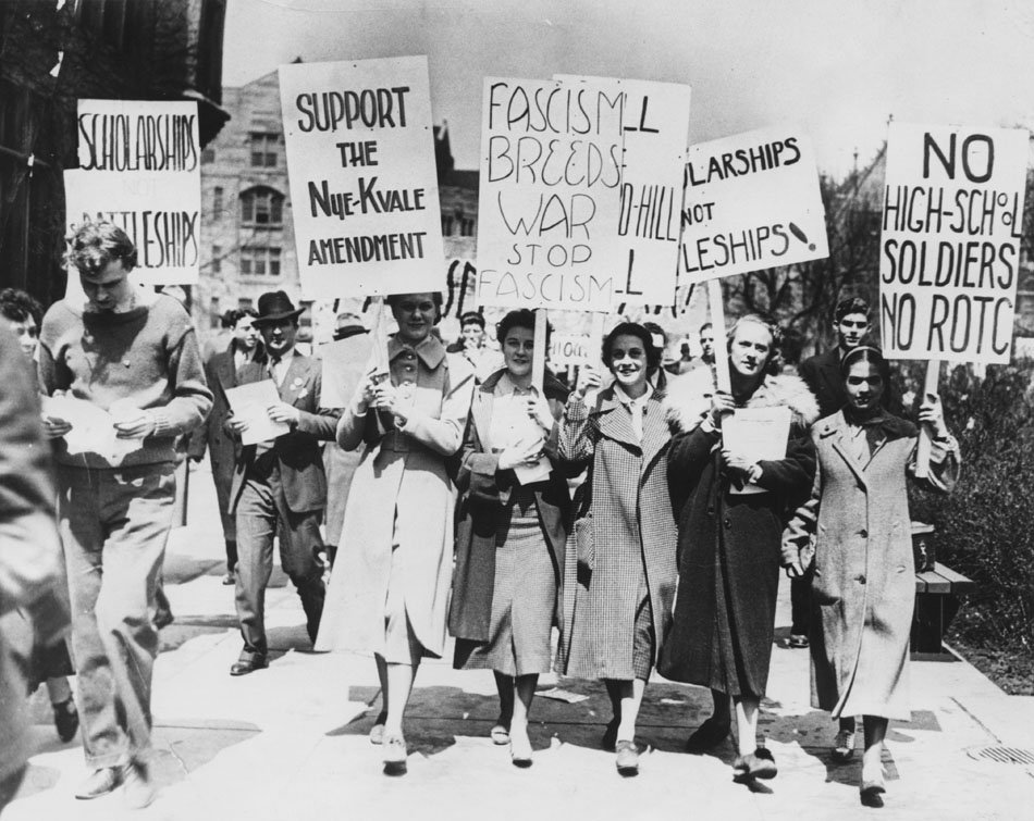 Women marching with protest signs against Fascism