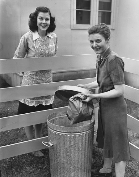 Two women talking over a garbage pail