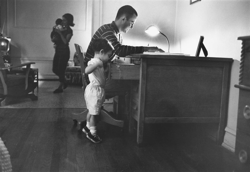 Male student working at desk with a child poking around in a drawer. Wife carrying another child can be seen in the background.
