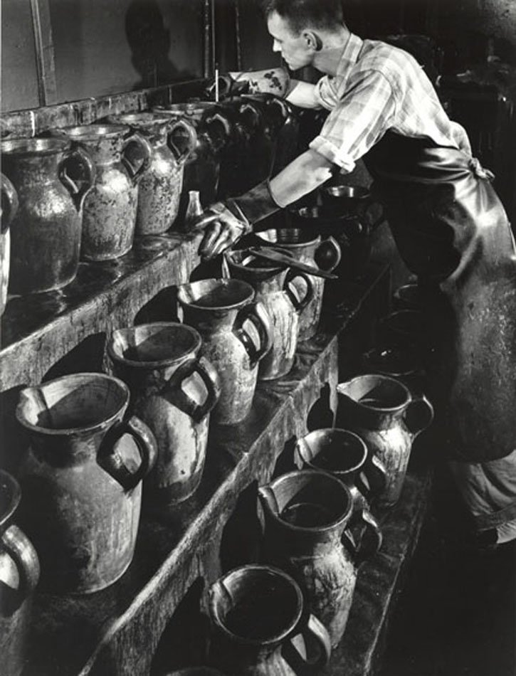 Man with rubber apron and gloves inspecting jugs with chemicals inside.