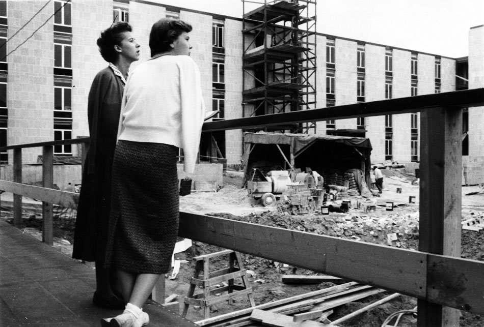 Two women looking out onto construction of a new dorm building