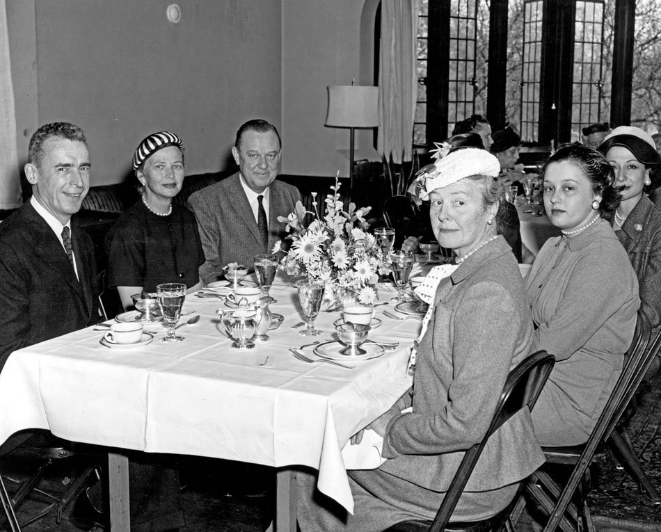 Men and women seated to dinner.
