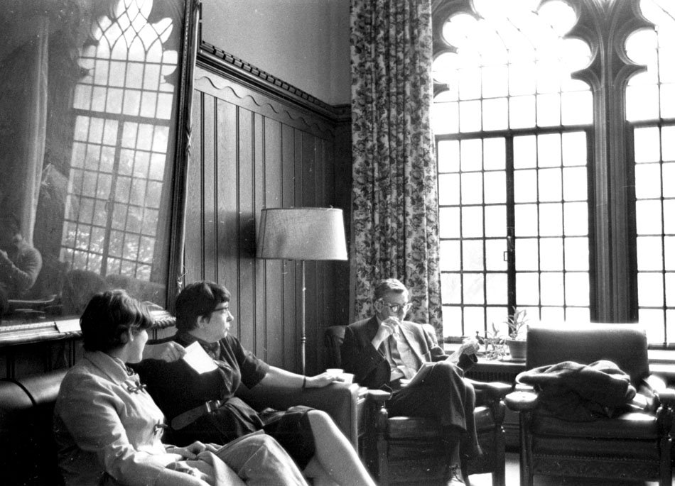 Two women and a man in discussion while relaxing on couches.