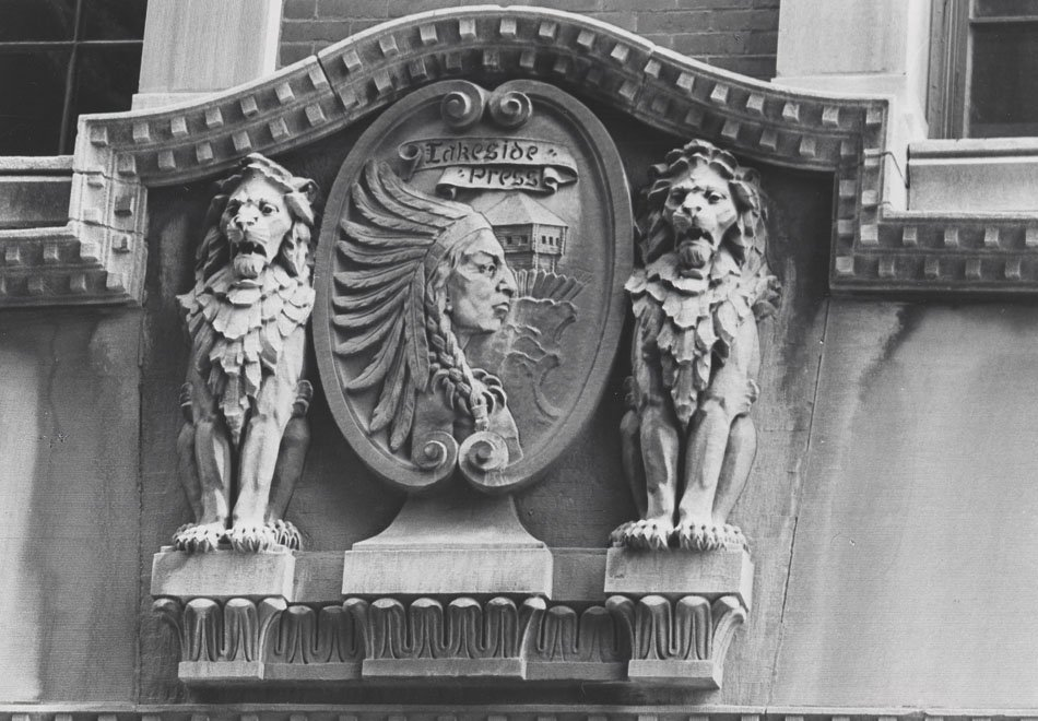 "Relief on the top of a building of a crest with lions flanking on either side. The crest says ""Lakeside Press."""