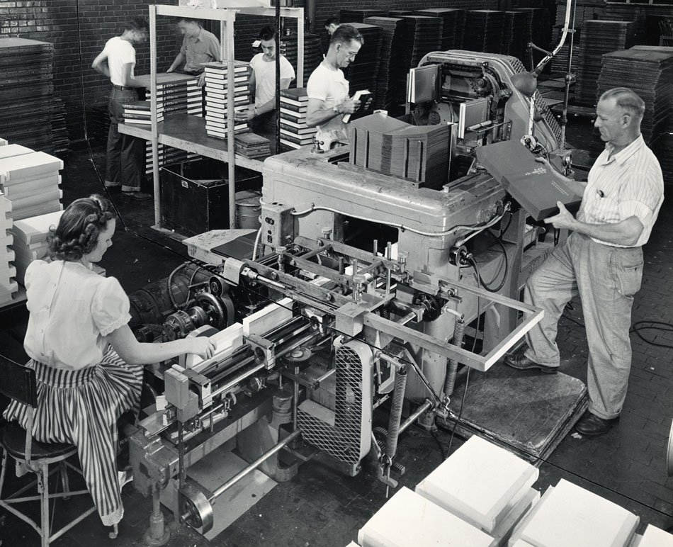 Photograph showing several workers on various machines, binding books