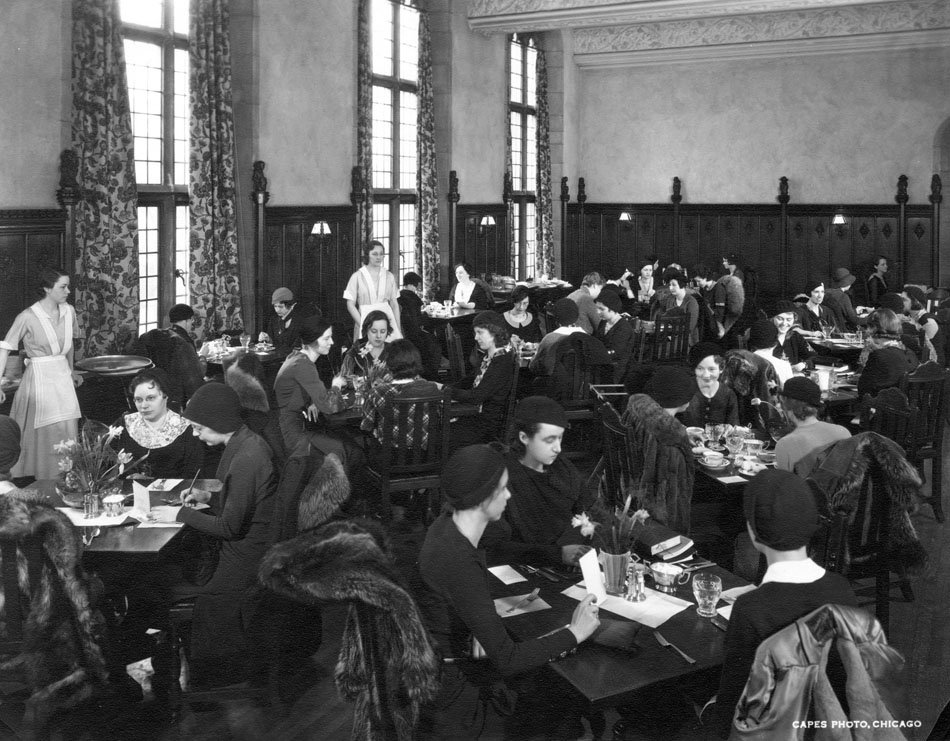Women seated at small tables eating