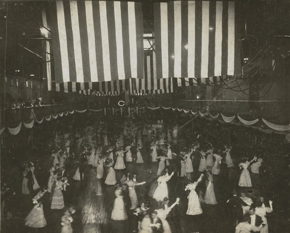 Large group dancing in the gym, strung with American flags