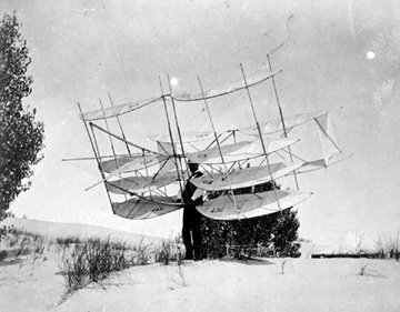 A multilayered flying machine with sails sits on a dune.