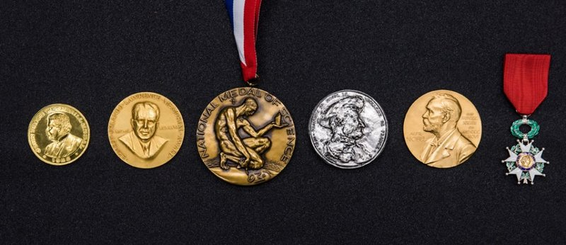 A row of silver and gold medals carved with various portraits of men.