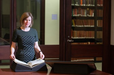 Elizabeth Frengel holds a rare book