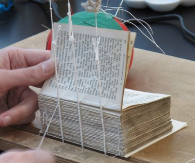Book binding being repaired by a preservation specialist