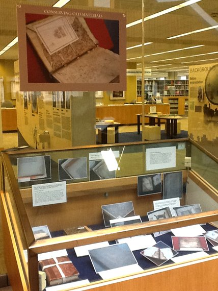 An exhibit case with various close-up photgraphs of books.