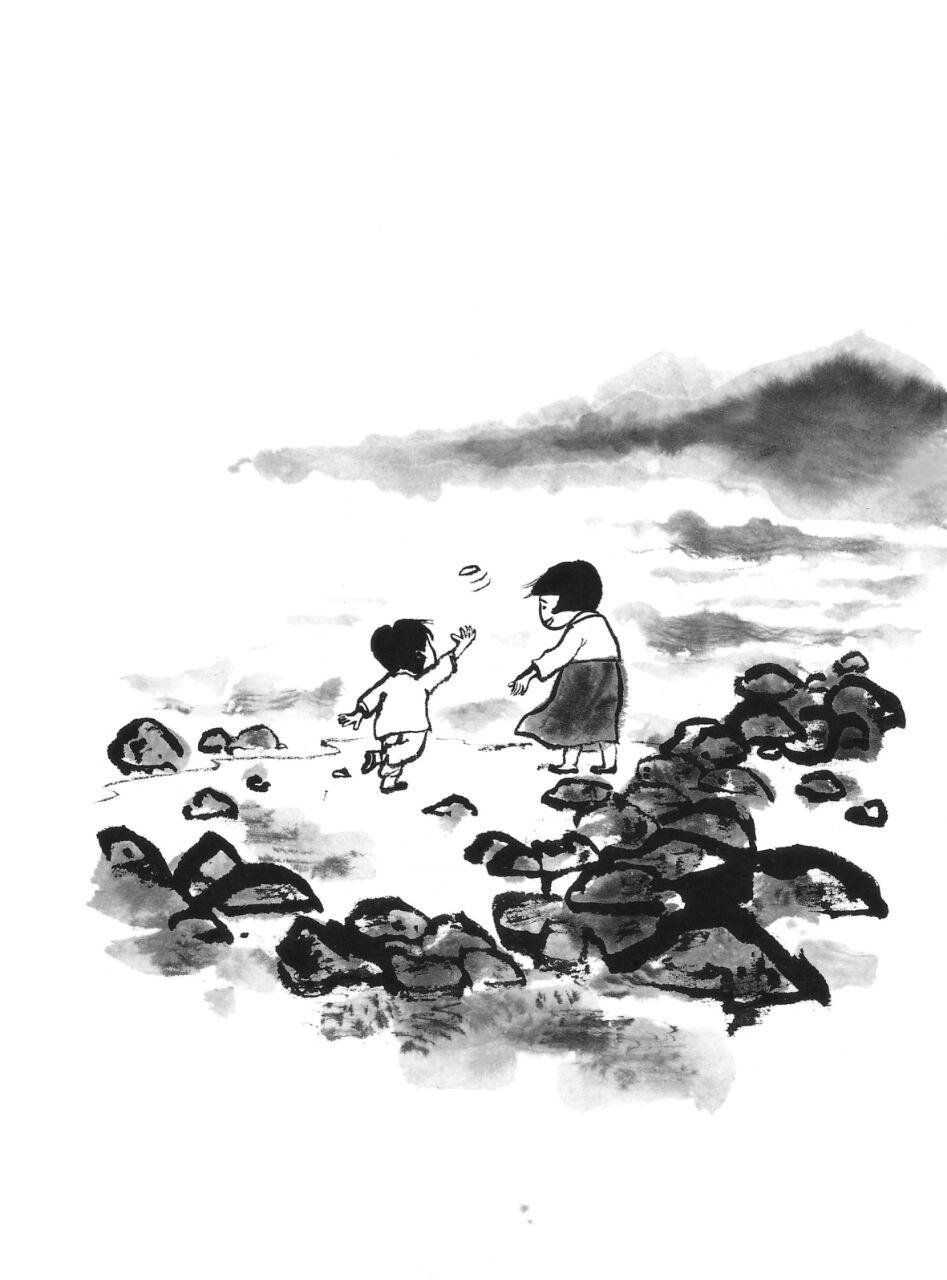 Two children play on a rocky shore.