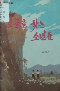 A book cover shows two boys at the foot of a high cliff.