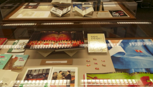 Glass cases hold various prints and books.
