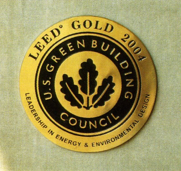 "A small round yellow-and-black plaque inscribed ""LEED Gold 2004."""
