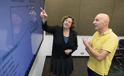 Stefano Allesina discusses a data management plan with Elisabeth Long, who points sto the plan on screen.