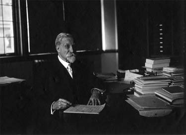 An elderly man with a beard sits at a desk crowded with papers.
