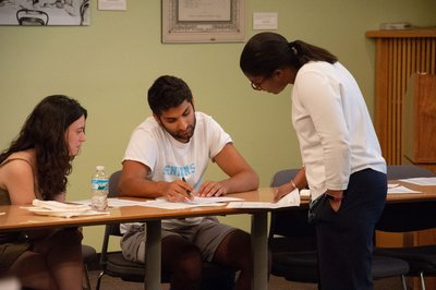 Elizabeth Foster (right) talks to two students, reviewing handouts