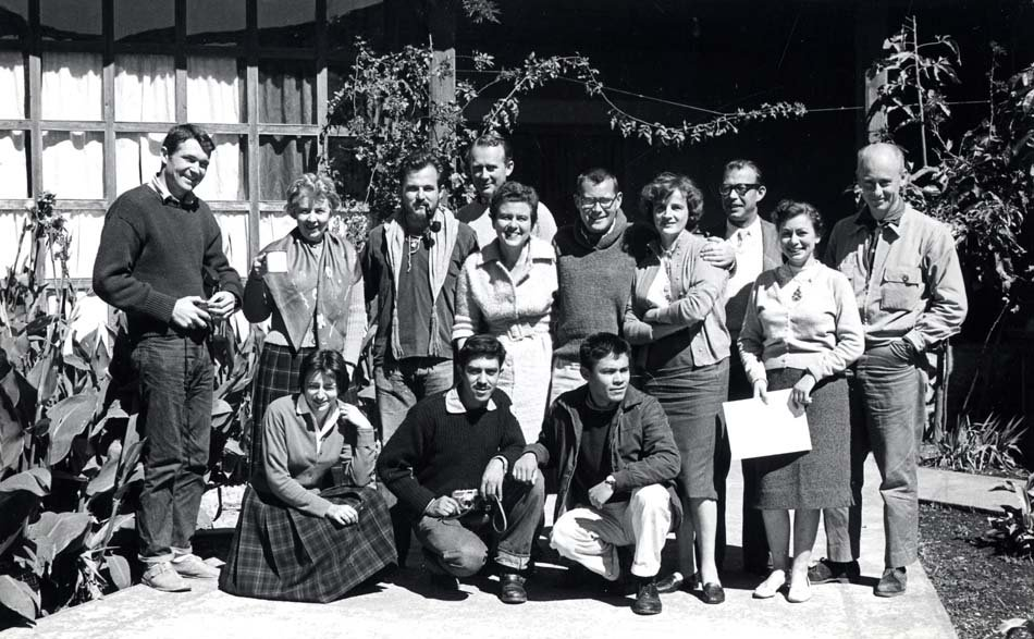 Black and white photo of thirteen people standing outside.
