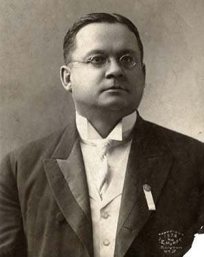 A man in glasses and a suit.