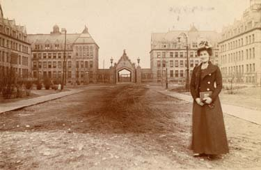 An old-fashioned photo of a woman in a field surrounded by Gothic buildings.