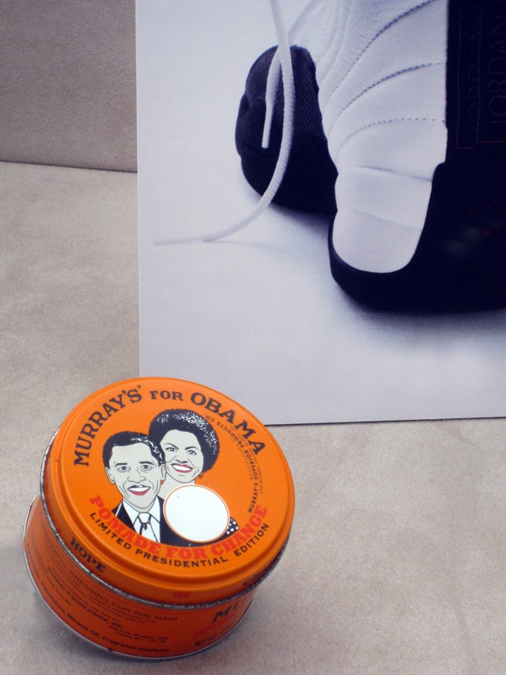 Ad showing a pomade tin with the Oboma's on it.