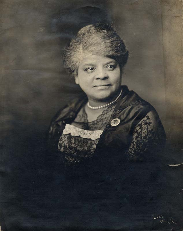 "Ida B. Wells pictured wearing a button she created to publicize a memorial service for African-American combatants court-marshalled and hanged in Houston, TX in the summer of 1917. The button reads ""In Memoriam Martyred Negro Soldiers Dec. 11, 1917."""