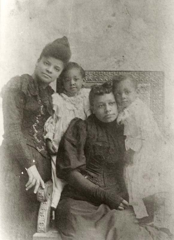 Ida B. Wells-Barnett (left), activist, journalist, teacher, and anti-lynching crusader. She is pictured with the family of Thomas H. Moss, Sr., Maurine, Betty, and Thomas, Jr. Mr. Moss, a postman and grocery store owner, was lynched in Memphis, Tennessee, 9 March 1892. The photograph was taken in Indianapolis, Indiana where his wife and children had relocated after the murder.
