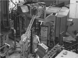 A large metal apparatus with many different parts filling an entire room. A man stands to its side.