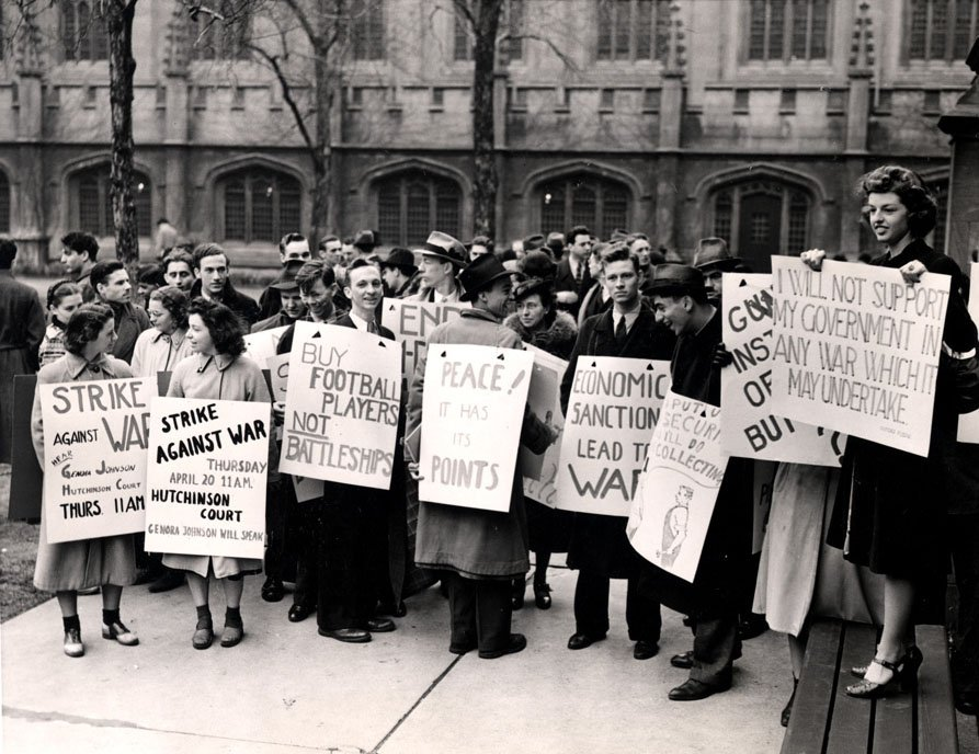 Group of students holding protest signs outside of a University building