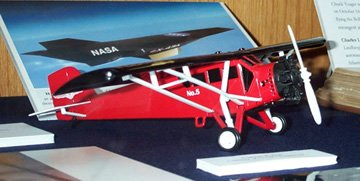 "A bright red WWII-era plane with ""NASA"" on its wing."