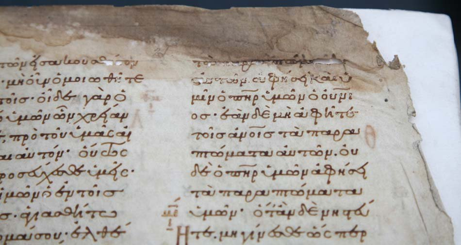 Close-up of parchment paper with damaged corner and writing showing through from other side.