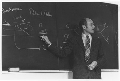 A suited man points to diagrams on a blackboard.