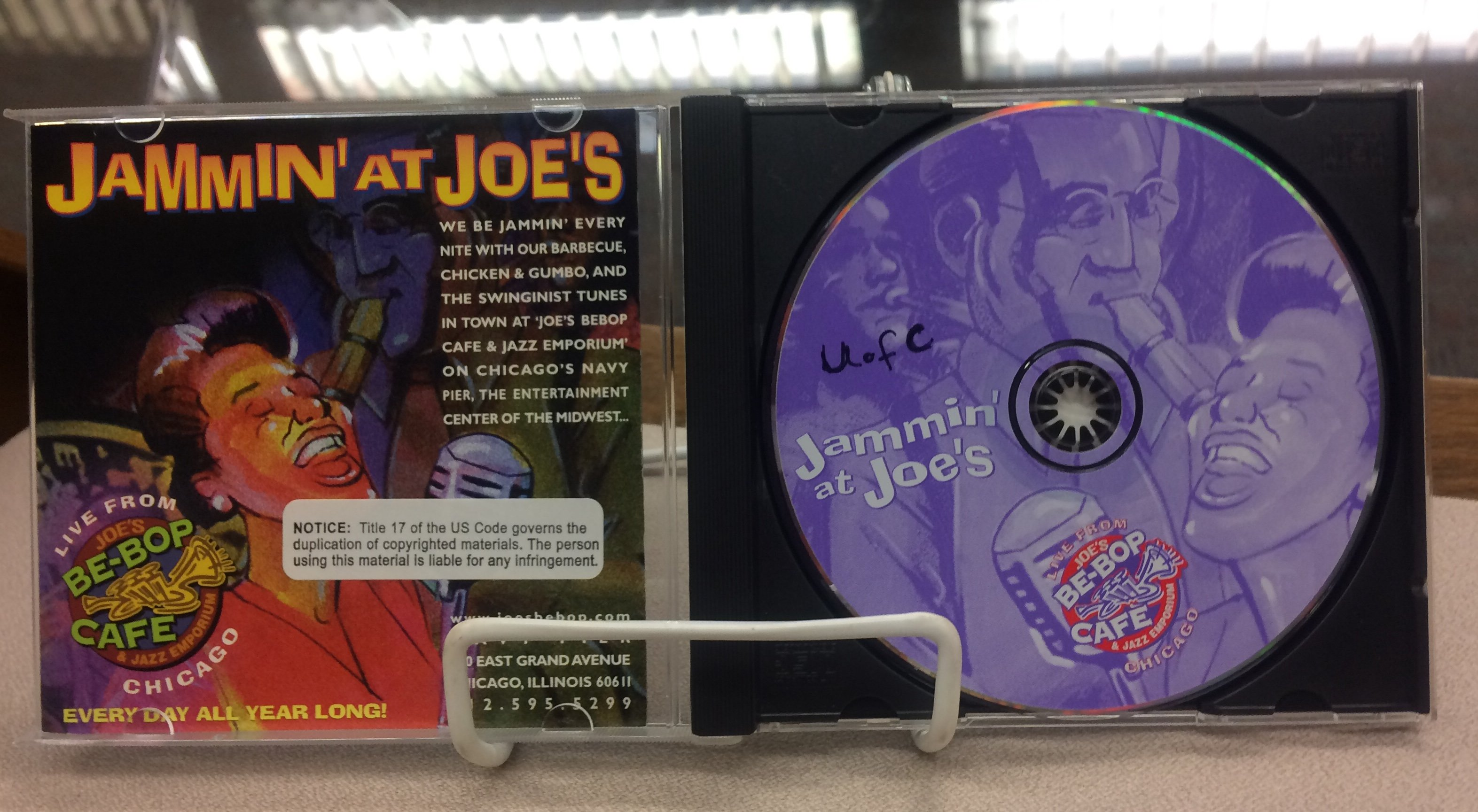 A CD case and a CD with illustrations of people playing instruments.
