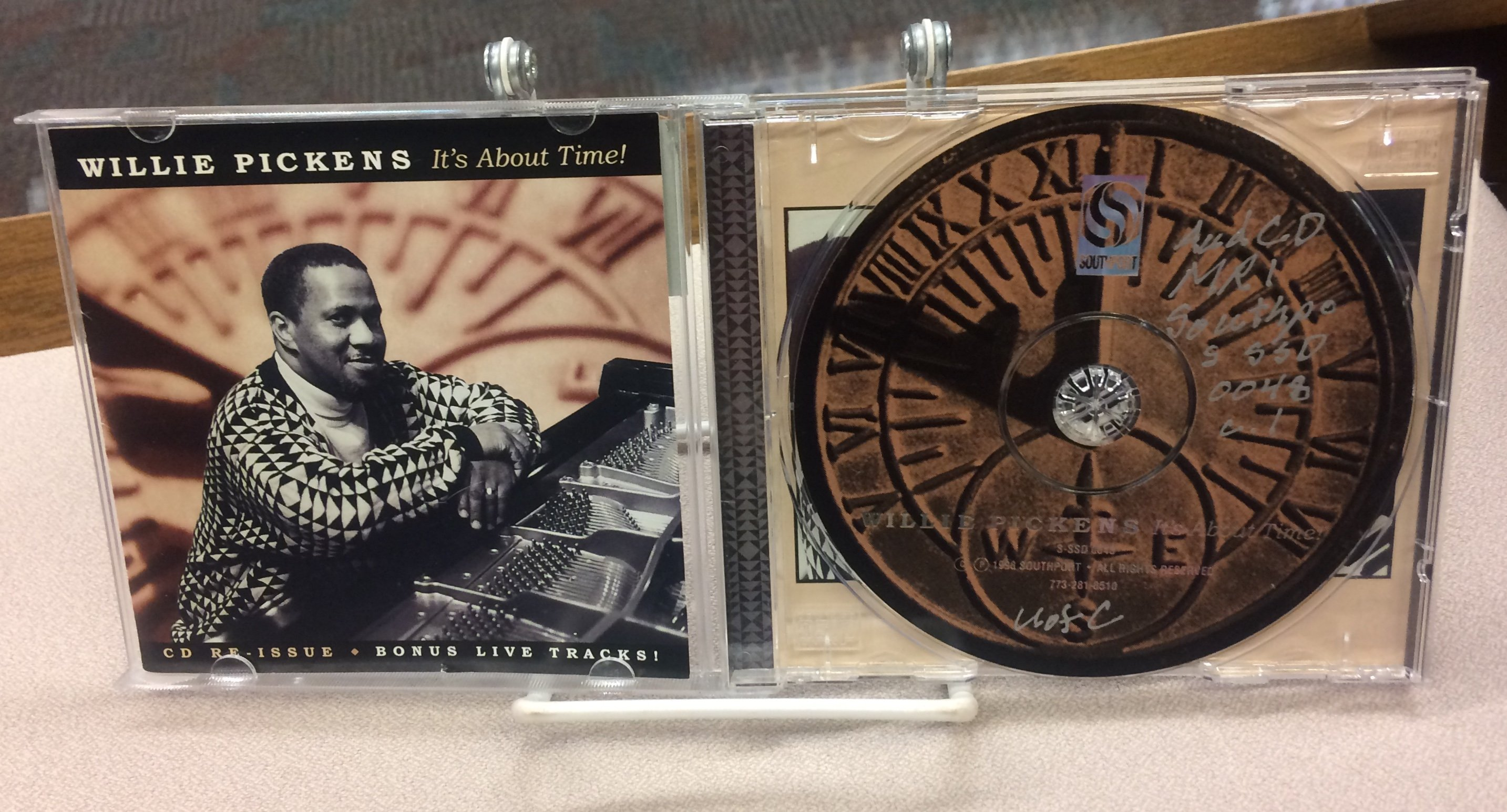 A CD case with the photograph of a man leaning against a grand piano, and a CD designed to look like a clock and a compass rose.