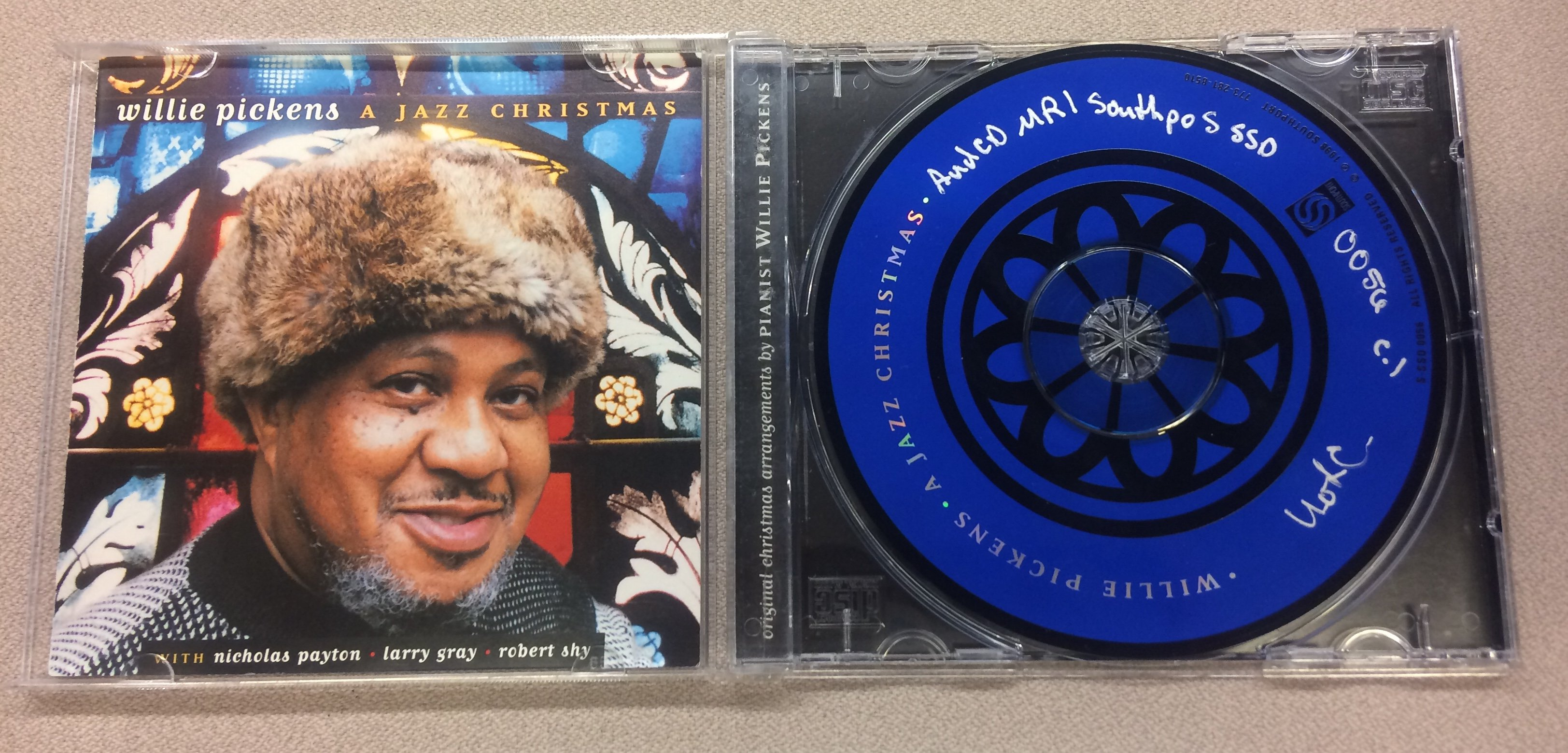 "A CD case titled ""A Jazz Christmas"" with a man in a fur hat, and the accompanying CD."