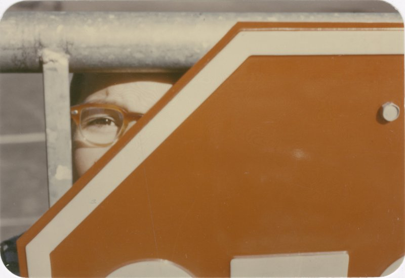 Photograph of part of a face (including an eye with glasses) behind part of a stop sign